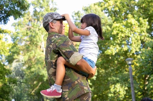 Papà serio in uniforme militare che tiene la figlia sulle mani, guardandola e in piedi all'aperto. piccola ragazza sveglia concentrata che tocca la protezione del padre. ricongiungimento familiare, paternità e concetto di fine settimana