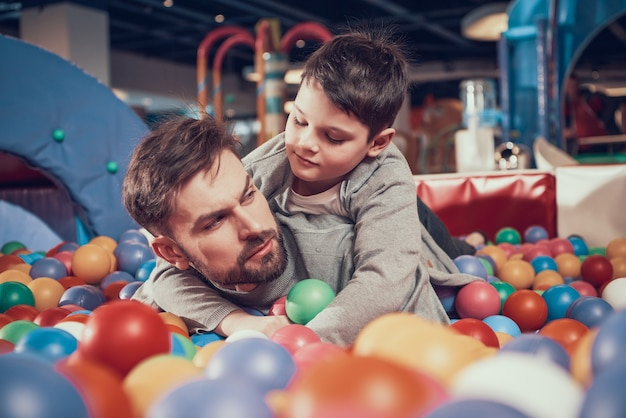 Serious dad and son in pool with balls in amusement park.