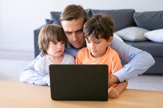 Papà serio che lavora al computer portatile e che abbraccia i figli. padre caucasico concentrato utilizzando laptop a casa. due simpatici ragazzi seduti in ginocchio. concetto di paternità, infanzia e tecnologia digitale