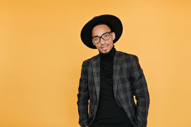 ポケットに手を入れて黄色の壁に立っている深刻な暗い目のムラートの男。カジュアルなスーツを着たアフリカの若い男の屋内写真は黒い帽子をかぶっています。