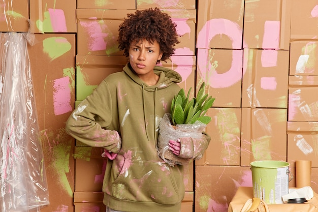 심각한 어두운 피부 곱슬 여자 바쁜 집을 개조하는 아파트 계획 집 수리에 페인트 그림 벽으로 더러운 캐주얼 셔츠를 입고 녹색 선인장의 냄비를 보유하고 있습니다. 집 수리 개념.