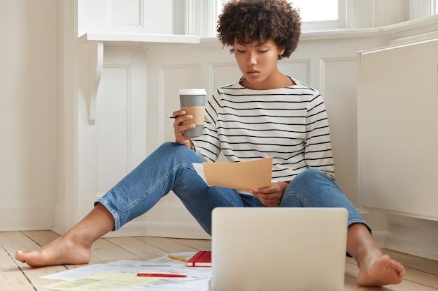 Серьезная темнокожая женщина-экономист думает о стартап-проекте, держит бумажный документ