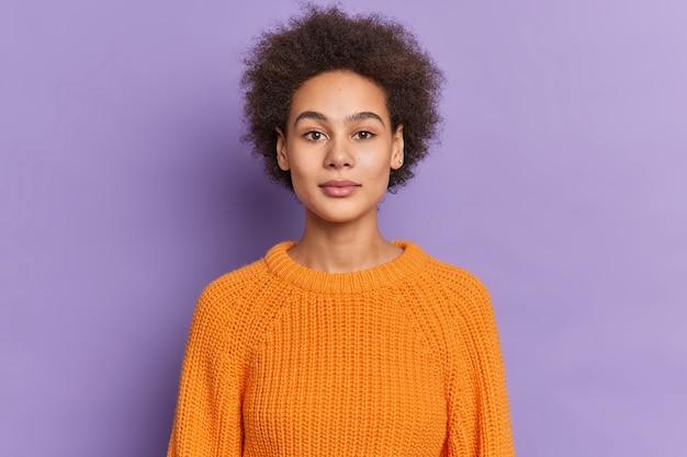 ふさふさした巻き毛の真面目な黒ずんだ10代の女性は、ニットのセーターを着た自然な美しさの落ち着いた表情を自信を持って見ています。