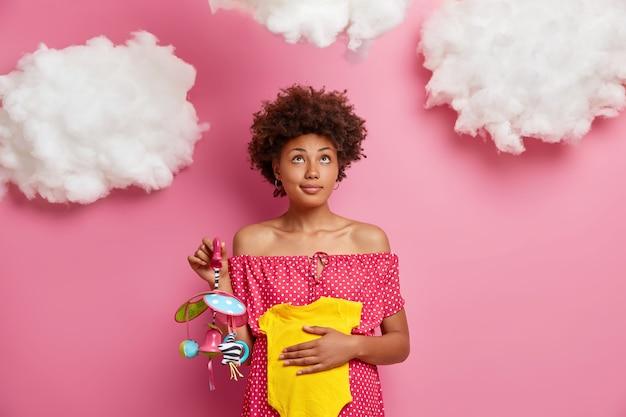 진지한 짙은 피부의 미래 엄마는 배가 큰 포즈를 취하며 아기가 아기 옷과 장난감을 위에 집중적으로 안고 사려 깊은 표정을 지을 것으로 예상합니다. 임신 모성과 기대 개념