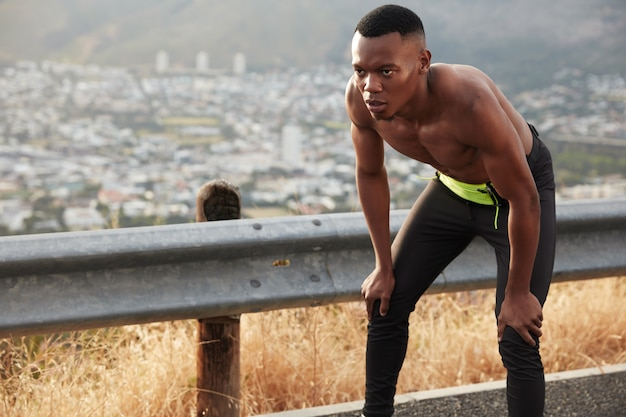 Serious dark skinned healthy man has determined facial expression, keeps hands on knees, poses topless at mountain road alone, has athletic body shape
