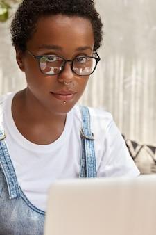 Un serio sviluppatore it dalla pelle scura installa un nuovo antivirus sul computer portatile, lavora in remoto, indossa gli occhiali