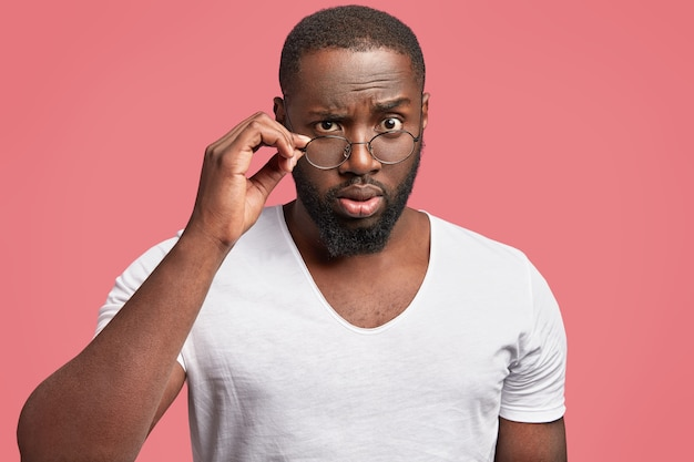 Serious dark skinned male professor looks in bewilderment through spectacles