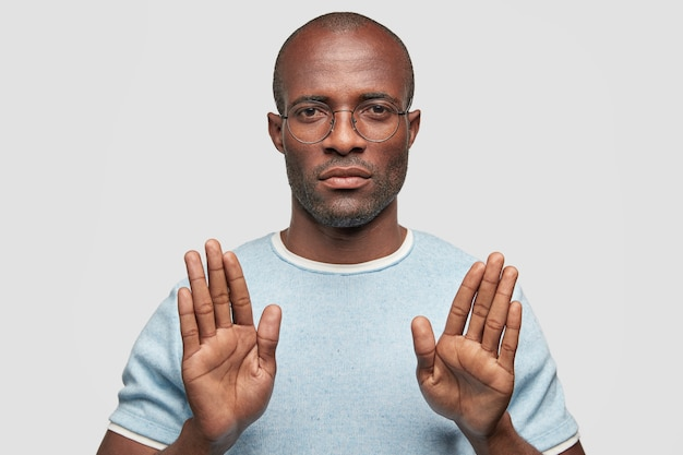 Serious dark skinned male shows stop gesture