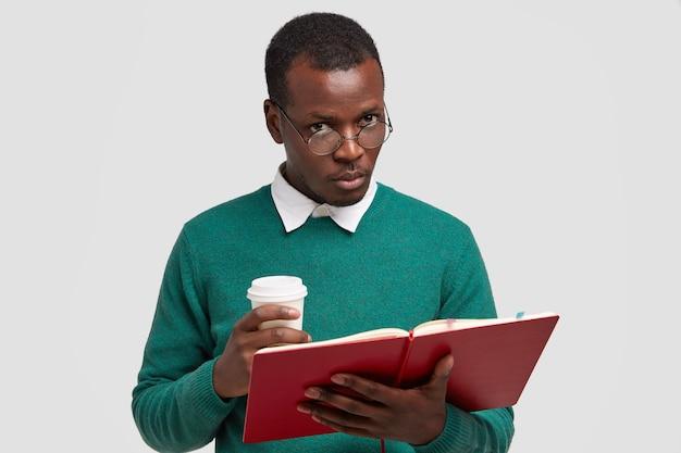 Un maschio serio dalla pelle scura ha i capelli corti, tiene in mano un libro di testo, porta fuori il caffè
