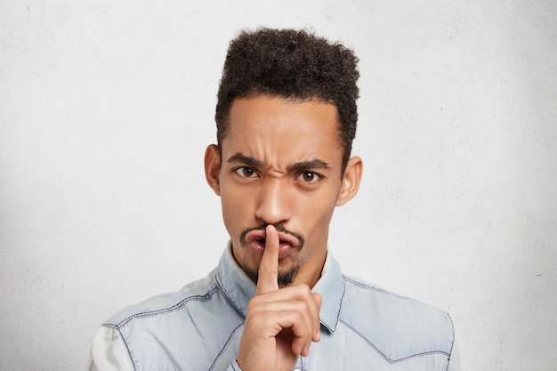 Serious dark skinned man makes silence gesture, says shh, asks to be quiet