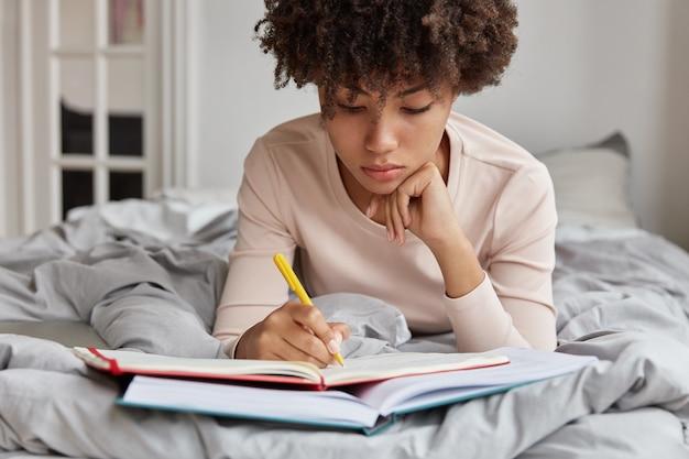 진지한 어두운 피부색의 학생은 이른 아침부터 시험을 준비하고, 책에서 노트에 중요한 메모를 쓰고, 자신의 방에서 만들어지지 않은 침대에 누워 있습니다.