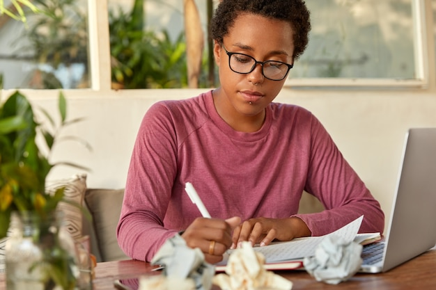 Serious dark skinned woman copywriter writes in sheet of paper