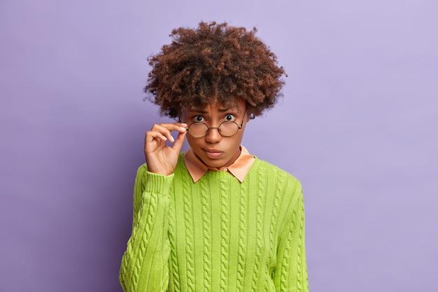 La donna dalla pelle scura seria ha lo sguardo fisso alla macchina fotografica tiene la mano sugli occhiali