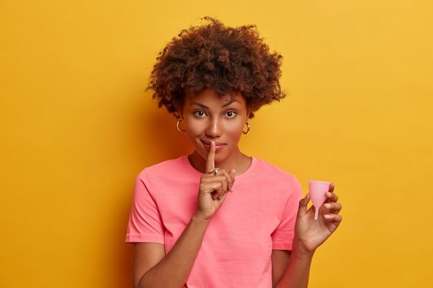 Una donna seria dalla pelle scura tiene la coppetta mestruale a forma di campana per l'inserimento nella vagina, intrappola il fluido mestruale e la protezione dalle perdite, racconta informazioni segrete e consigli su come usarlo, fa segno di silenzio