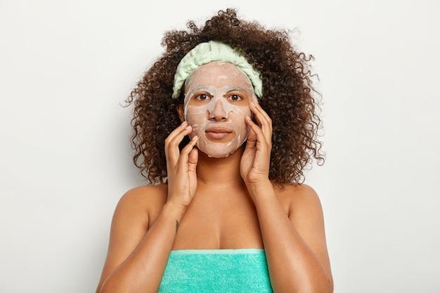 진지한 어두운 피부의 여성은 천연 시트 마스크를 착용하고 얼굴 피부에 관심이 있으며 덤불처럼 바삭 바삭한 머리카락을 가지고 있으며 직접 보이며 수건으로 싸여 있습니다.