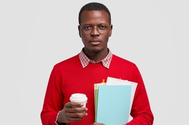 Grave giovane dalla pelle scura con espressione facciale sicura di sé, pronto per lo studio, tiene libri di testo e caffè da asporto, pone su uno spazio bianco
