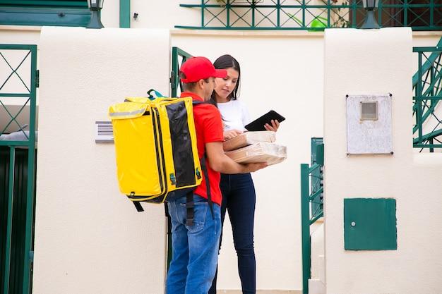 小包を持っている真面目な配達員と注文をチェックしている女性。赤いキャップと黄色の保温バッグが付いたシャツのコンテンツ宅配便で、徒歩でエクスプレスオーダーを提供します。配送サービスとポストコンセプト