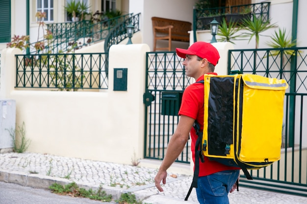 Fattorino serio in cerca di indirizzo e porta borsa termica gialla. corriere attraente in camicia rossa che cammina lungo la strada e consegna l'ordine. servizio di consegna di cibo e concetto di acquisto online
