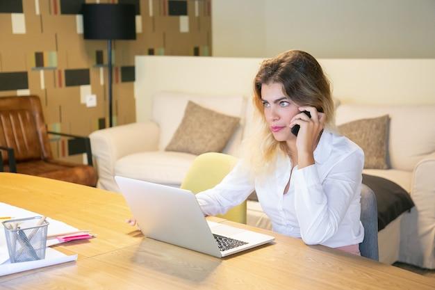 Designer serio che discute del progetto con il cliente sul telefono