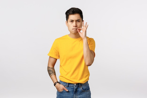 Serious and determined asian male model in yellow t-shirt, with tattoos, suck lips shut mouth, making zip gesture near lips as if secure and telling not tell something, keep secret, silence concept