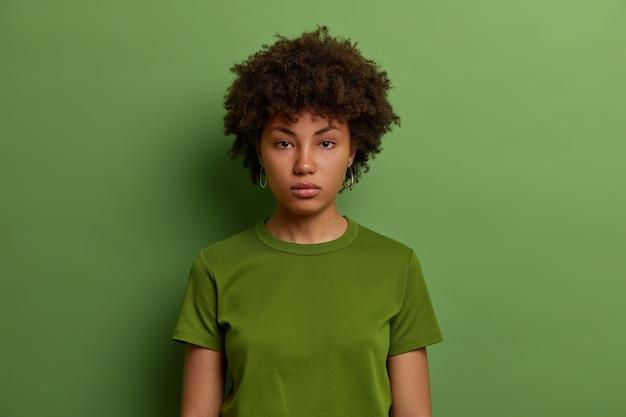 진지하게 결정된 밀레 니얼 아프리카 계 미국인 여성이 직접적으로 보이고, 자신감이 있고, 캐주얼 한 녹색 티셔츠를 입고, 실내에서 포즈를 취하고, 정보를 듣고, 곧바로 사업을 시작합니다.