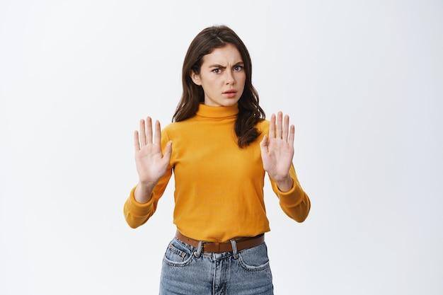 La donna seria e determinata dice di no, mostrando il gesto di proibire e proibire, chiedendo di calmarsi o rifiutare qualcosa di brutto, accigliato, in piedi sul muro bianco