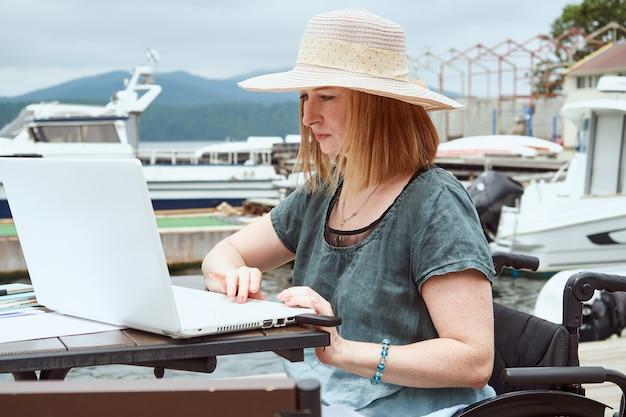 深刻な障害のある女性は、カフェでラップトップを使用しています。在宅勤務、トレーニング。