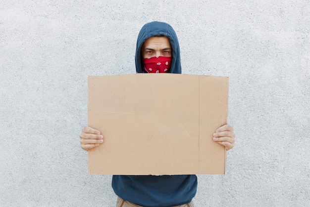 Серьезный разочарованный протестующий с банданой на лице и картоном