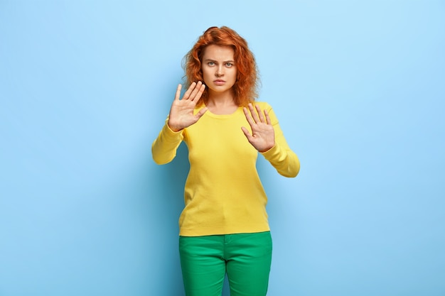 Serious discontent woman has wavy red hair, shows stop gesture, keeps palms outstretched at camera, refuses something