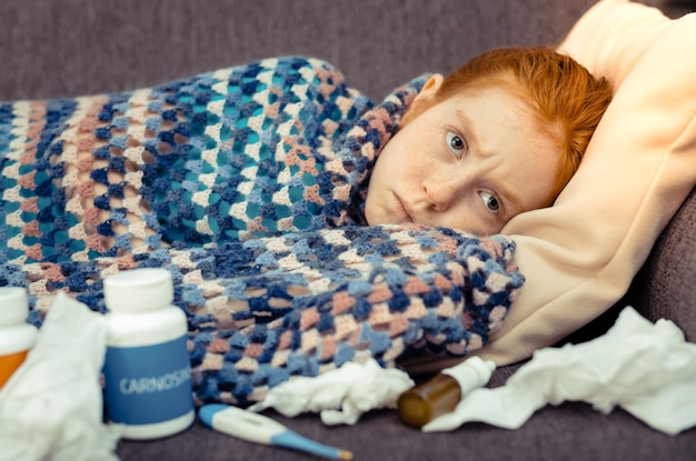 Serious disease. depressed cheerless girl resting on the sofa while being sick
