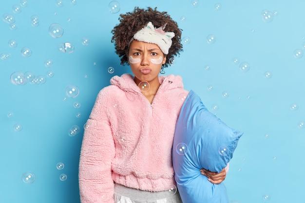 深刻な不機嫌なアフリカ系アメリカ人の女性が巻き毛の口唇を怒ってカメラを見て怒って朝早く目を覚ます枕を保持