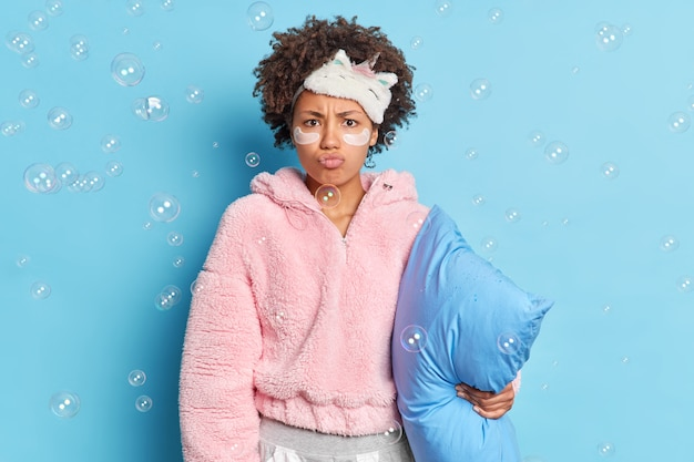 Serious displeased afro american woman with curly hair pouts lips looks angrily at camera awakes early in morning holds pillow