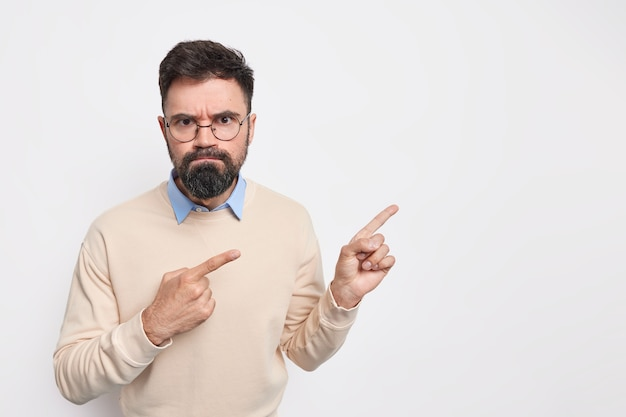 Серьезный недовольный бородатый европеец со скептическим выражением лица чувствует недовольство, ругает кого-то в круглых очках и свитере