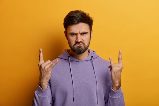 Serious displeased bearded man rocker makes horn sign with fingers, has charismatic face expression, frowns face, wears purple sweatshirt, attends rock concert, isolated over yellow wall.