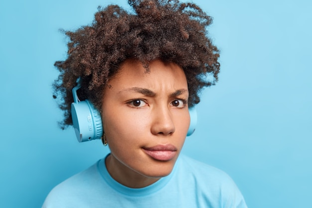 Serious displeased curly haired african american woman wears stereo wireless headphones looks attentively  listens music or audio book dressed casually isolated over blue wall.