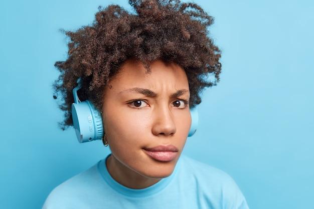 Серьезная недовольная кудрявая афроамериканка в беспроводных стереонаушниках смотрит внимательно, слушает музыку или аудиокнигу, одетая небрежно изолированно на синей стене.