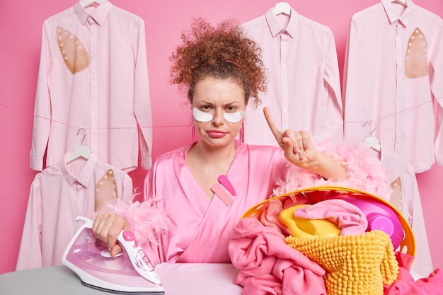 Serious displeased femae housekeeper looks angrily  raises index finger asks to wait one minute finished ironing laundry applies pads under eyes to reduce wrinkes wears dressing gown
