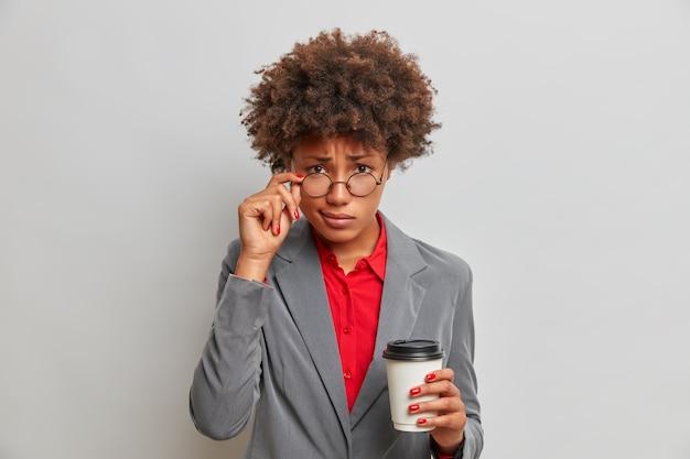 Serious displeased female employee looks through transparent glasses