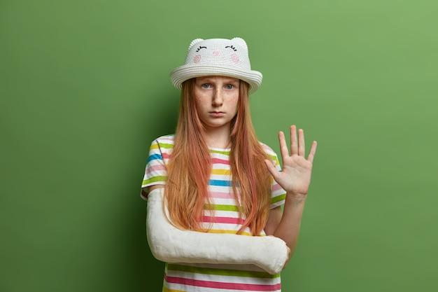深刻な不機嫌な悲観的な悲しい少女は、気分を害した表情で見え、手のひらを振って、誰かに挨拶し、負傷した壊れた腕に包帯を巻いて、緑の壁に隔離されています。子供の怪我。