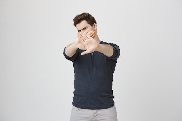 Serious displeased guy showing stop, make cross gesture