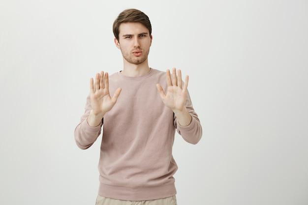 Serious displeased man show stop, refusal gesture, raise hands in disagreement
