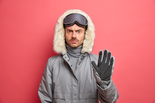 Serious displeased man skier in winter clothes wears ski goggles on head keeps palm forward makes stop gesture.