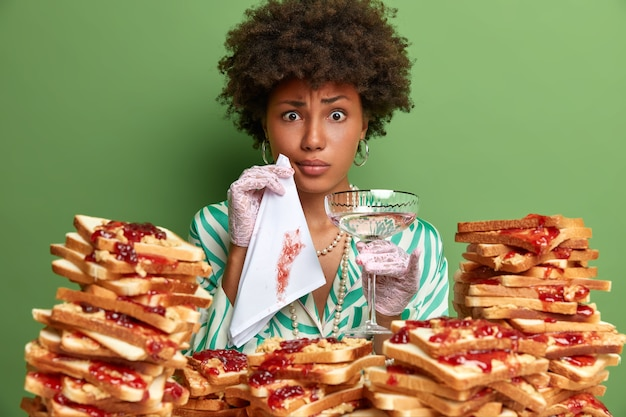 Serious displeased woman looks awkward, wipes dirty mouth with napkin, dressed elegnatly, holds glass of alcoholic beverage, poses near pile of bread, isolated on green wall. lady in restaurant
