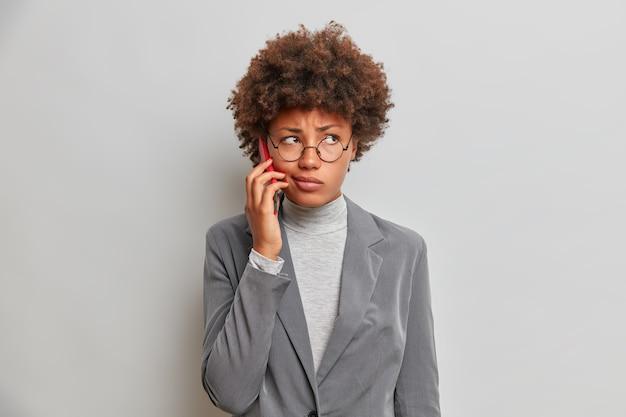Серьезная недовольная женщина разговаривает по современному мобильному телефону с недовольным выражением лица, сосредоточенным в стороне, носит официальную одежду, позирует в помещении