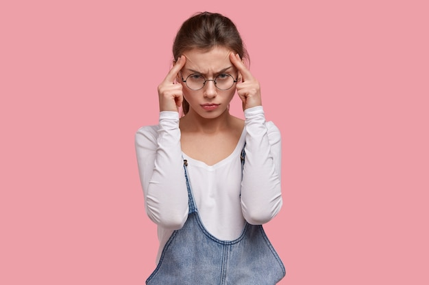 Una donna seria e scontenta cerca di concentrarsi e concentrarsi sul lavoro, tiene le mani sulle tempie, ha un terribile mal di testa, riduce il dolore causato dagli antidolorifici