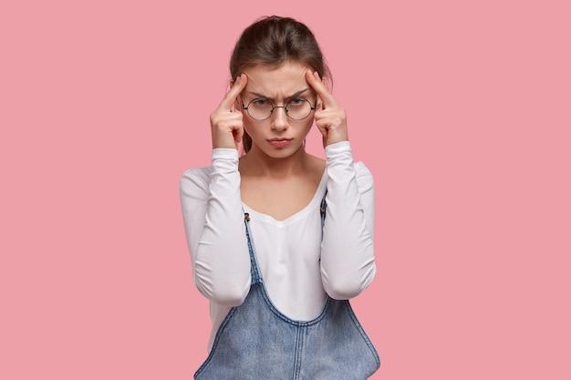 심각한 불쾌한 여성은 일에 집중하고 집중하려고하며, 관자놀이에 손을 대고, 끔찍한 두통을 겪고, 진통제로 인한 통증을 줄입니다.