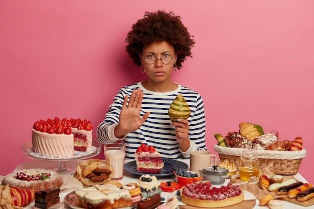 아프로 헤어 스타일을 가진 심각한 불쾌한 여성은 거절 제스처를 보여주고, 크로와상을 들고, 디저트를 먹지 않으며, 안경과 줄무늬 점퍼를 착용합니다.