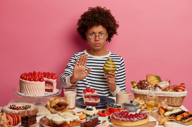 Serious displeased woman with afro hairstyle shows refusal gesture, holds croissant, denies eating dessert, wears spectacles and striped jumper