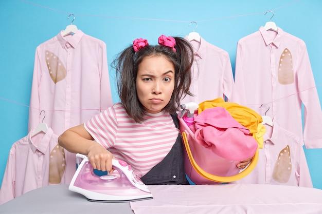 深刻な不機嫌な若いアジアの家政婦は、洗濯物のバケツを運ぶ忙しいアイロンをかけている服の笑い顔