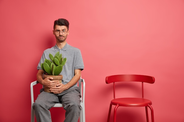 Serious dissatisfied caucasian man in casual wear rests in chair holds potted cactus stays at home